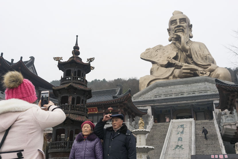 Tourists take photos at the entrance of Yuanfu Wanning Temple, Jurong City, Jiangsu province, Jan. 10, 2017. The complex includes a massive statue of Lao-tzu, the founder of Taoism. Thomas Cristofoletti for Sixth Tone