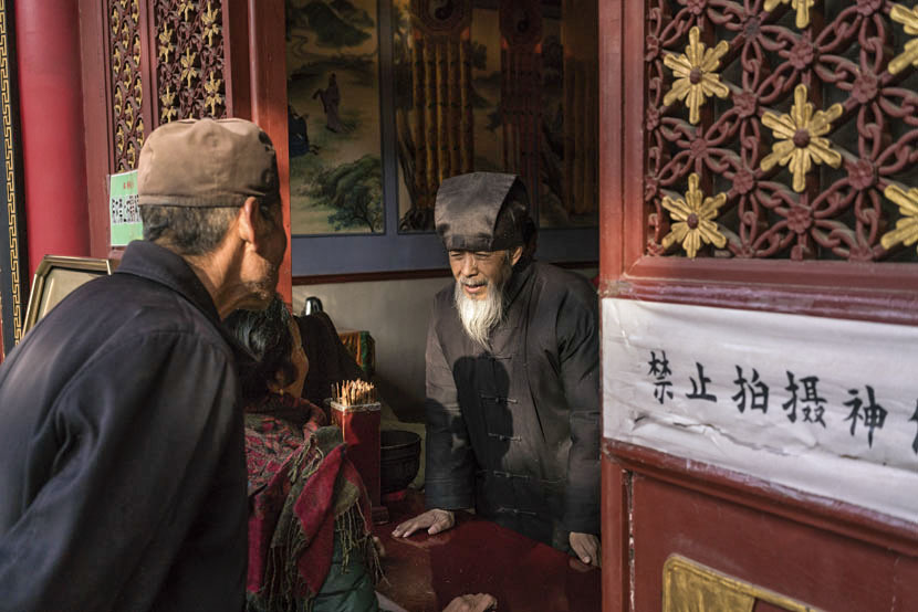 A Taoist monk helps visitors prepare an offering at Louguantai Temple, Tayu Village, Shaanxi province, Jan. 12, 2017. Thomas Cristofoletti for Sixth Tone