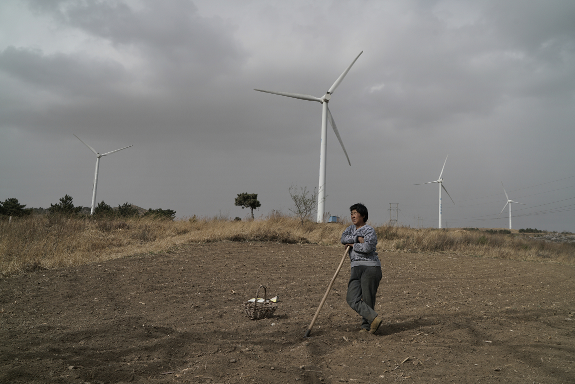中外对话 dialogue and the environment up on the hill you can hear the new turbines spinning in the strong breeze chen fang from the village of taizigou hopes the wind will bring rain so she