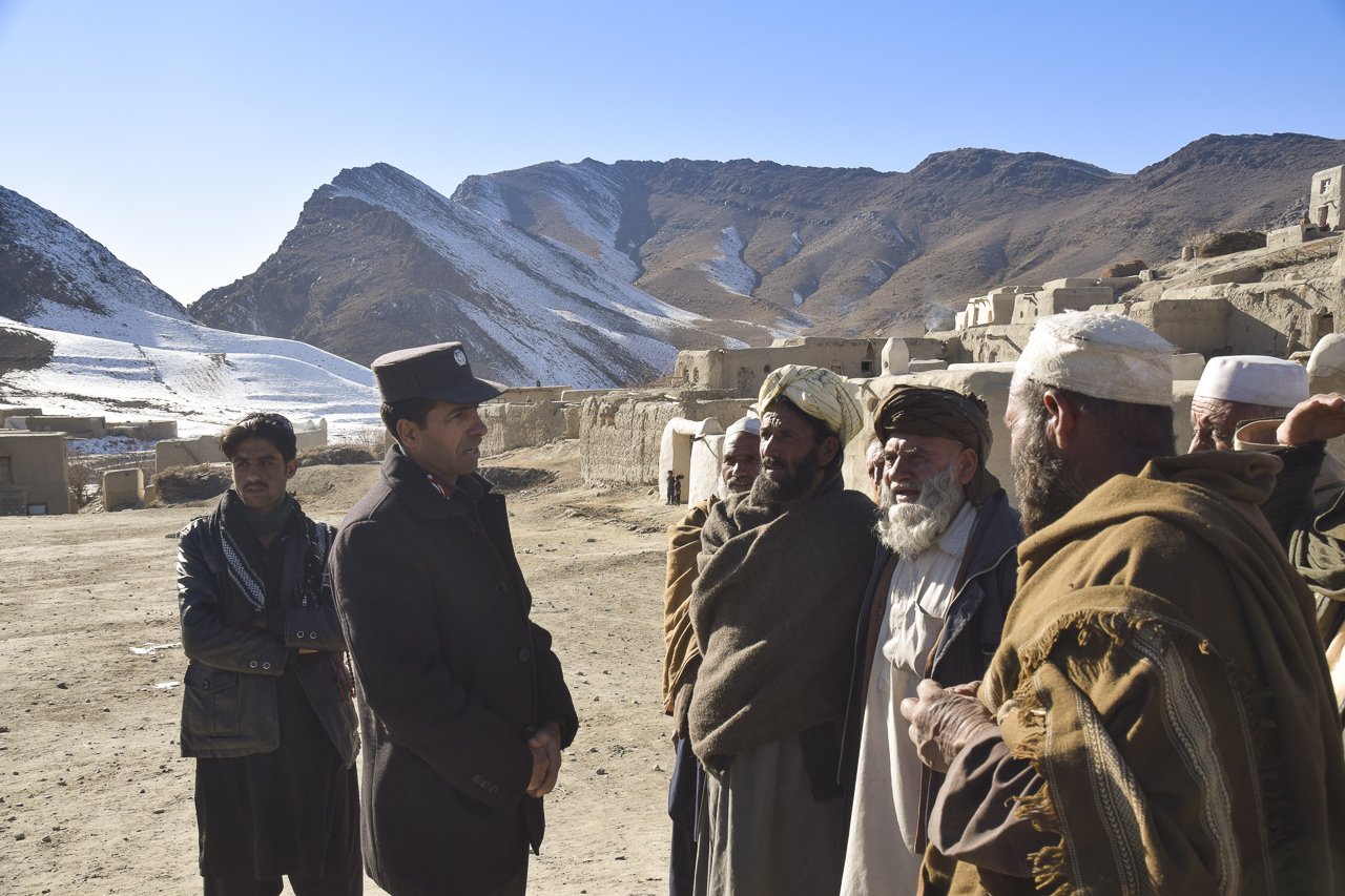 Concerned villagers talk with an officer of the Afghan Public Protection Force in Pochai, one of at lwast two still inhabited villages inside the mining area of Mes Aynak
