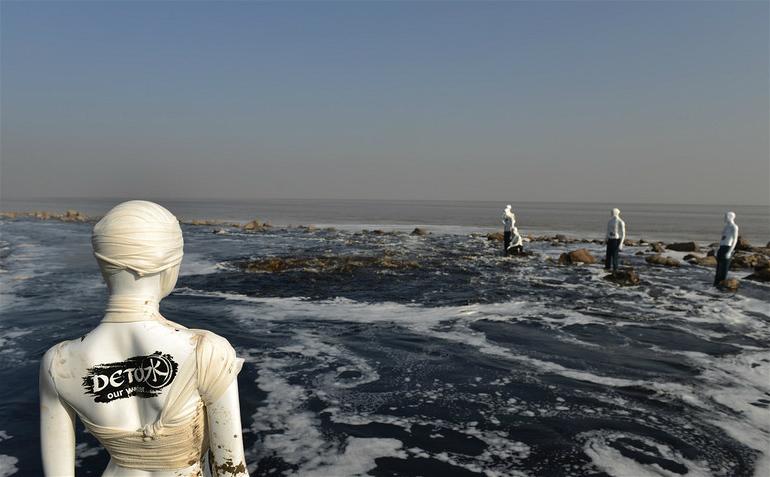"""写有""""去毒""""字样的橱窗模特,被环保志愿者安装在中国浙江的一个纺织印染废水排放口附近,呼吁纺织行业清除有毒有害化学品"""