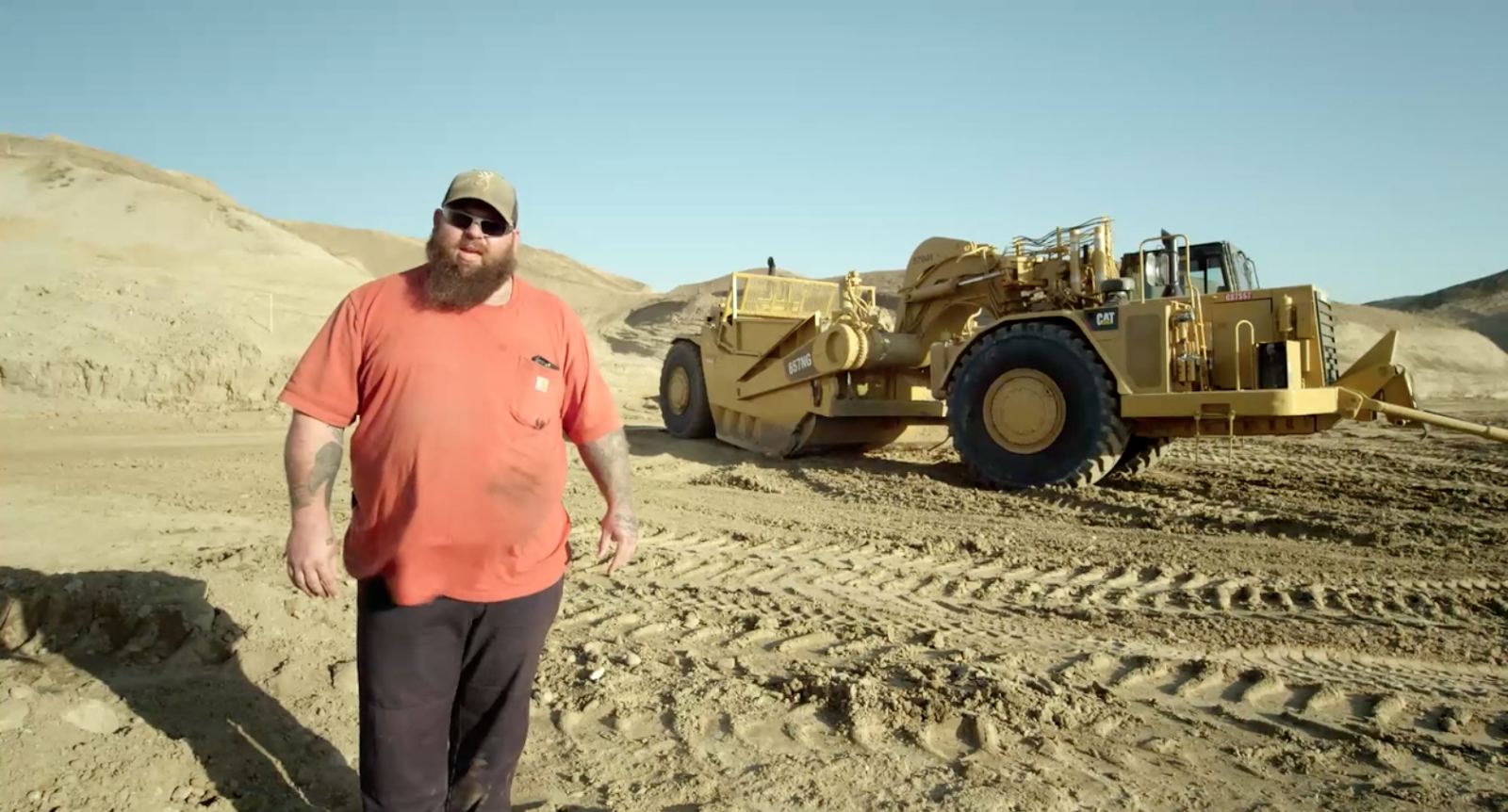 Steven Kuzar standing in front of the Caterpillar truck in the San Fernando Valley from documentary film Earth