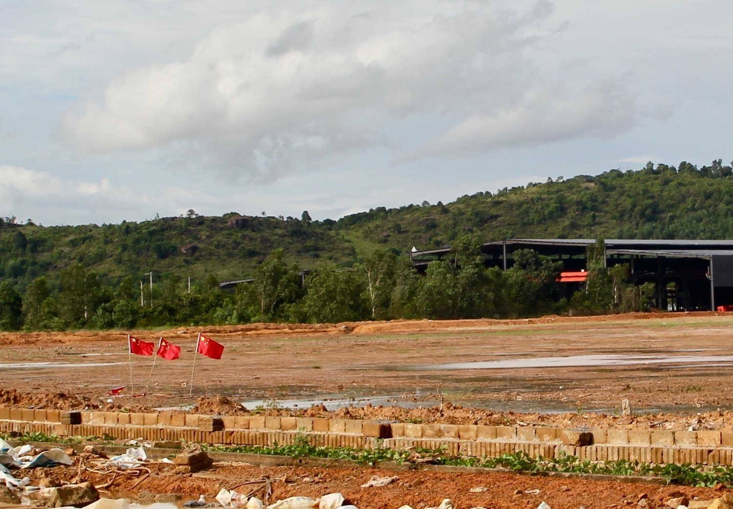 Chinese flags fly over an industrial lot under development in Sihanoukville (Image: Lili Pike)