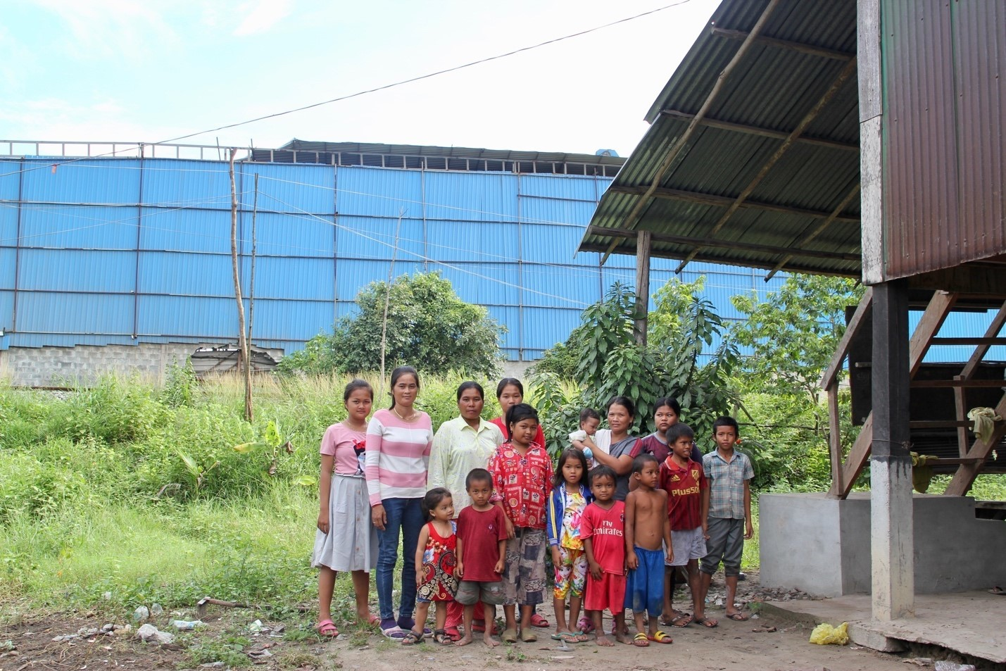 Peng Mom, Phok Nge, their children, and other neighbours with the coal ash processing plant behind them (Image: Lili Pike)