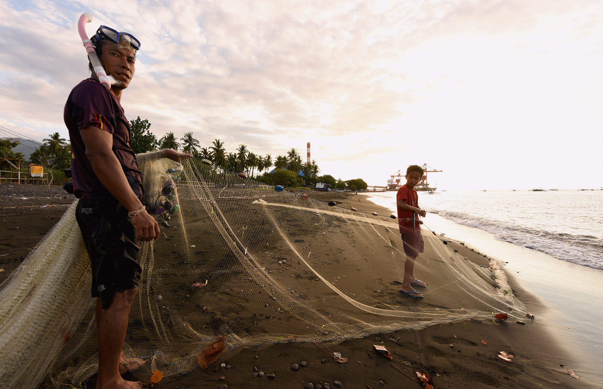 A fisher and his son on Celukan Bawang beach near the power plant (Image: Ade Dani)
