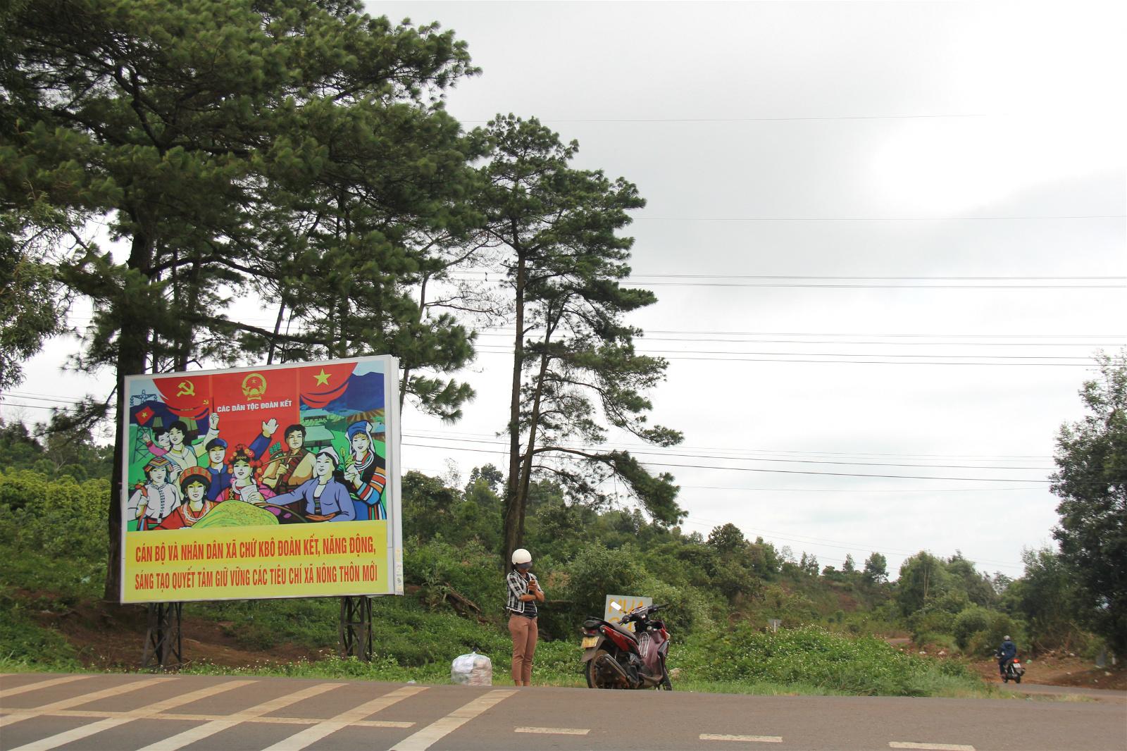 """邦美蜀乡村公路上的宣传画:""""政府和民众要团结起来下定决⼼保持已经实现的新农 村标准"""""""