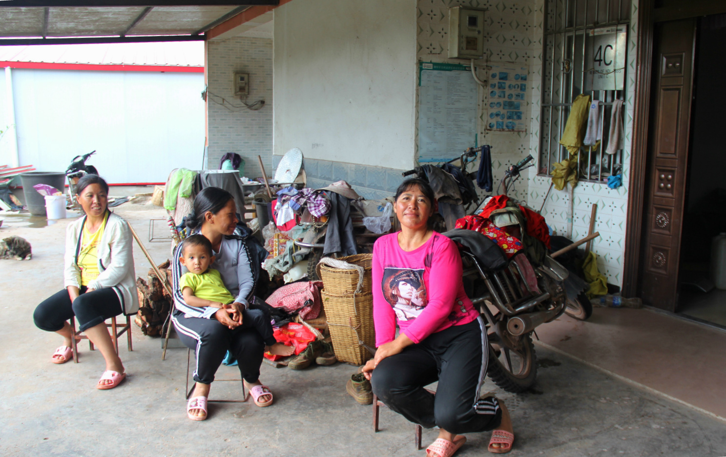 Farmer Li Yemei (first on the right) sits out of her house with her friends