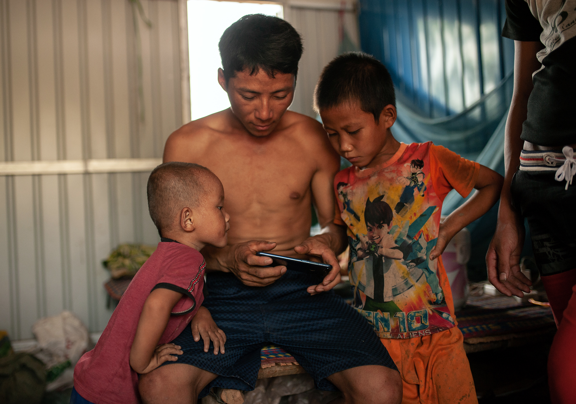 Worker and his children play a game on a Huawei phone he brought a month ago for 1 million LAK or 100 USD. (Image: Visarut Sankham/China Dialogue)